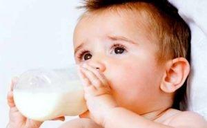 грудничок пьет молоко из бутылочки